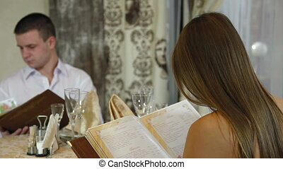 Menu - young couple dinner in a restaurant