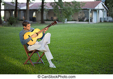 Man Playing Guitar in Lawn - Full length of casual relaxed...