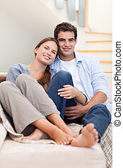 Portrait of a couple lying on a sofa while looking at the...