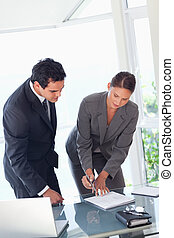 Businesswoman showing partner where to sign - Young...