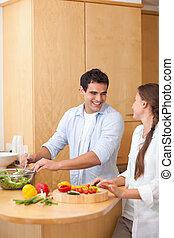 Portrait of a couple preparing a salad