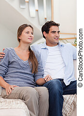 Portrait of a couple watching a movie in their living room