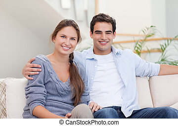 Couple posing in their living room while looking at the...