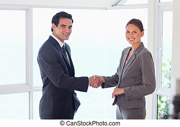 Side view of smiling trade partner shaking hands - Side view...