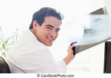 Side view of smiling doctor with x-ray