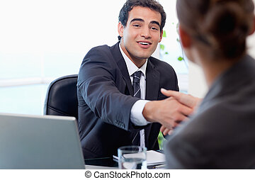 Smiling manager interviewing a female applicant in his...