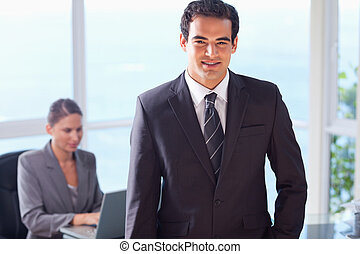 Smiling businessman with colleague behind him