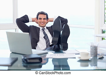 Happy businessman relaxing in his office