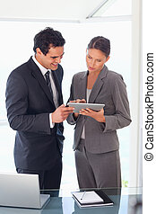 Business partner looking at tablet together - Young business...