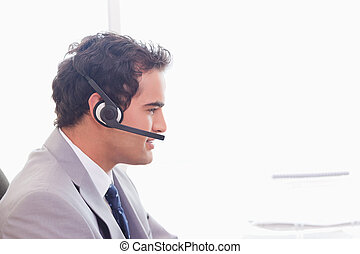 Side view of businessman with headset on - Side view of...