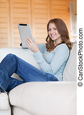 Smiling woman with tablet relaxing on sofa - Smiling young...