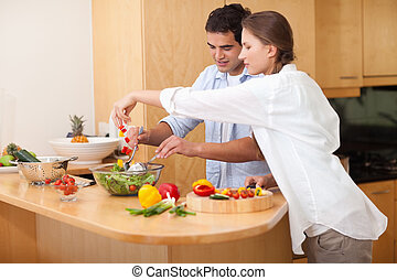Happy couple preparing a salad in their kitchen
