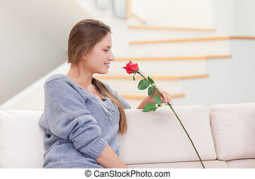Woman smelling a rose in her living room