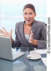 Portrait of a surprised businesswoman working with a...