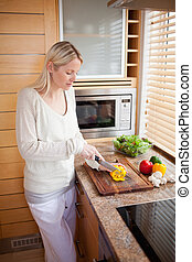 Side view of woman cutting bell pepper - Side vie of woman...
