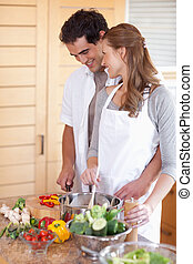 Smiling couple preparing meal together - Happy smiling...