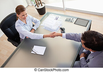 Above view of consultant shaking hands with her client -...