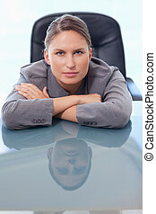 Portrait of a young businesswoman leaning on her desk