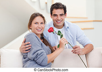 Young man offering a rose to his wife