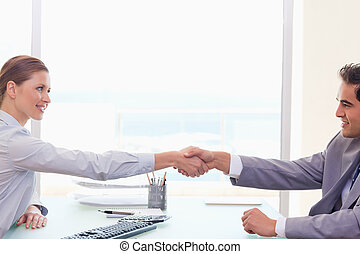 Trading partner shaking hands - Young trading partner...