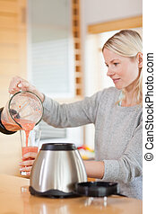 Side view of woman pouring self made smoothie - Side view of...