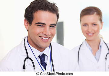 Smiling assistant doctors standing next to each other -...