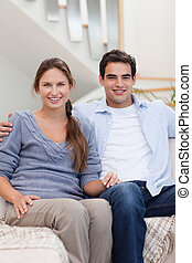 Portrait of a couple sitting on a sofa while looking at the...