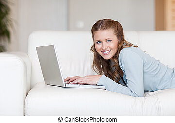 Cheerful smiling woman on the couch typing on her laptop