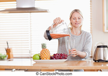 Woman pouring self made juice into a glass - Woman pouring...