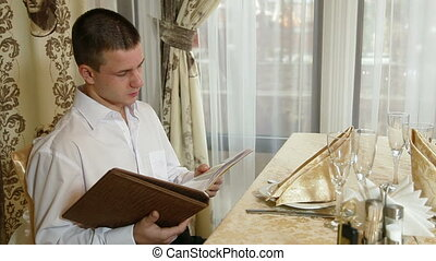 choice dishes from menu - young man chooses a meal in the...