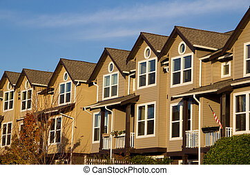 Row of Townhomes on Sunny Day - Three-story townhomes facing...