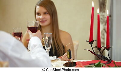 couple toasting at a restaurant table DOF focusing on on...