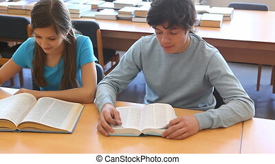 Reading textbooks - Pupils reading textbooks then looking at...