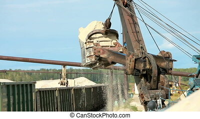 Working excavator - Excavator unloading sand in the bucket...