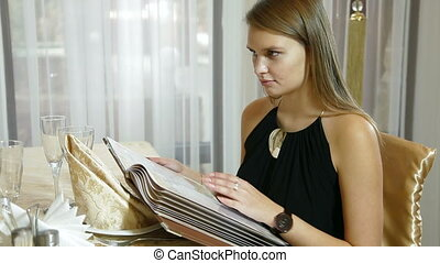 choice dishes from menu - young woman chooses a meal in the...