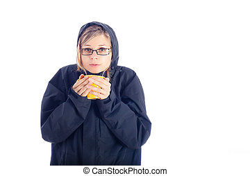 Woman in winter jacket holding mug with hot drink.