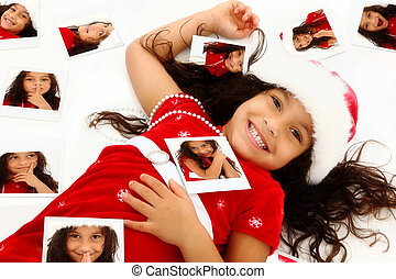 Beautiful Hispanic African American Girl Child in Santa Hat Christmas Dress surrounded by self polaroid portraits on floor.