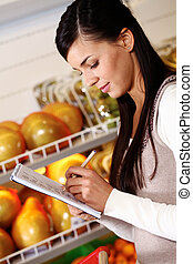Girl buying products - Image of pretty woman ticking what...
