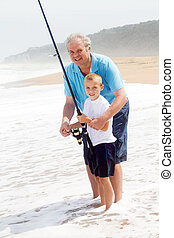 grandpa teaching grandson fishing on the beach