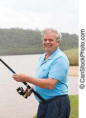 happy senior man fishing by the river