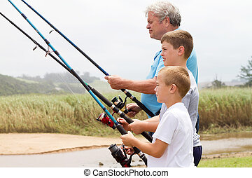 senior man fishing with his grandsons