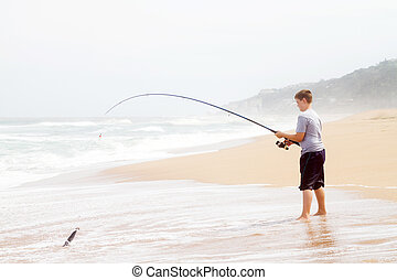 teen boy fishing on beach - teen boy pulling a fish out of...