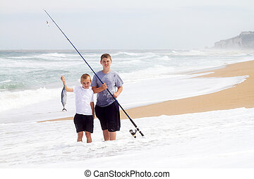 two boys catching a big fish on beach