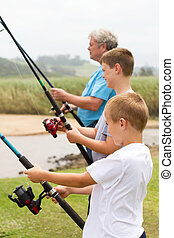 boys fishing with their grandpa - two boys fishing with...