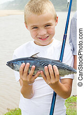 happy boy showing a fish he caught - happy little boy...