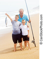 catching a big fish on beach - grandpa and two grandson...