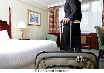 Woman in Hotel Room - Woman standing with baggage in hotel...