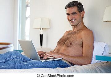 Shirtless Man Working on Laptop - Portrait of smiling...