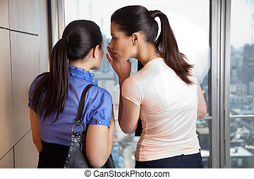 Female Whispering to Co-worker - Two female co-workers...