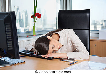 Tired business woman sleeping on the keyboard in office